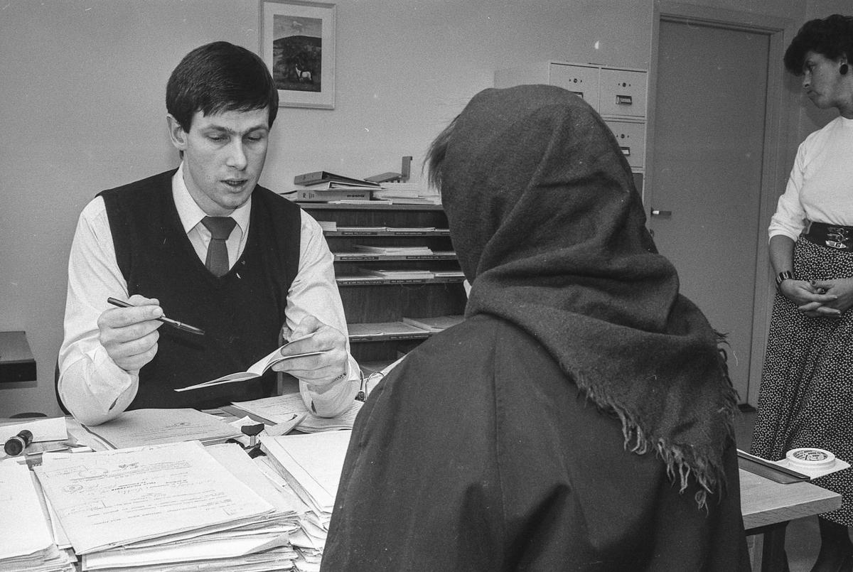 Fremmedkontoret i Ski. Politioverkonstabel Vidar Avlesen i samtale med en innvandrerkvinne i skaut. Arrangert bilde.