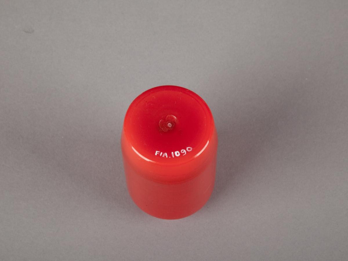 Lyslykt innsamlet etter terrorhandlingen 22. juli 2011 fra minnesmarkeringene i Lillestrøm.   Det er fire gravlykter. Dette er en liten lyslykt til utendørsbruk i rød plast. Lyktens fasong er enkel med rette linjer. Den er litt smalere nederst og enda ett hakk smalere øverst - som et vanlig syltetøyglass. En liten rest av hvit stearin ligger igjen i bunnen av lykten sammen med den runde metallbiten som holdt veken på plass. I metallbiten sitter fortsatt en sort rest av veken, i tillegg er det små flekker av rust på biten. Noen helt få partikler av sot sitter også i stearinen i bunnen av beholderen. Et tynt lag av stearin har også festet seg langs stort sett hele kanten innvendig. Støpeskjøtene synes på lykten/beholderen utvendig.