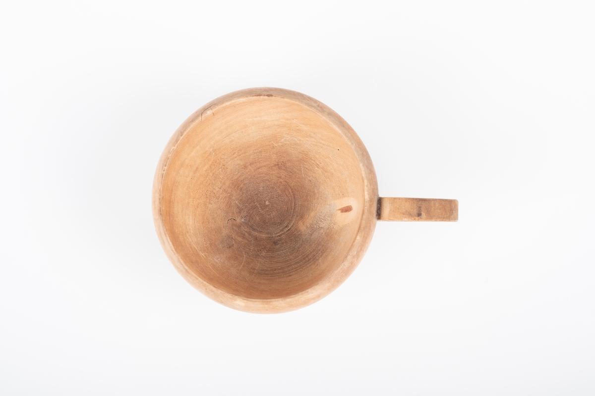En rund kopp med rund hank i treverk. Treverket er ubehandlet. Det er påført tekst på framsiden av koppen.