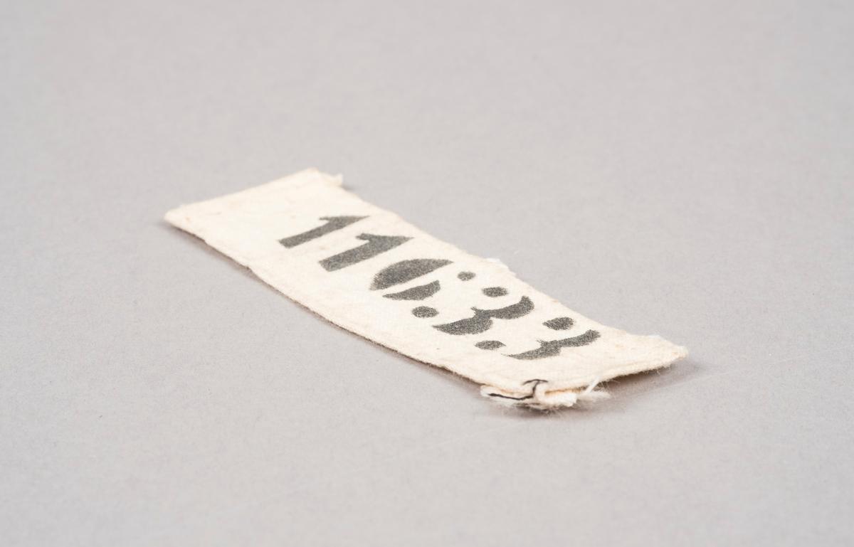 Merkelapp i naturhvitt lerretsstoff med nummeret 11633 trykket på med sort blekk.