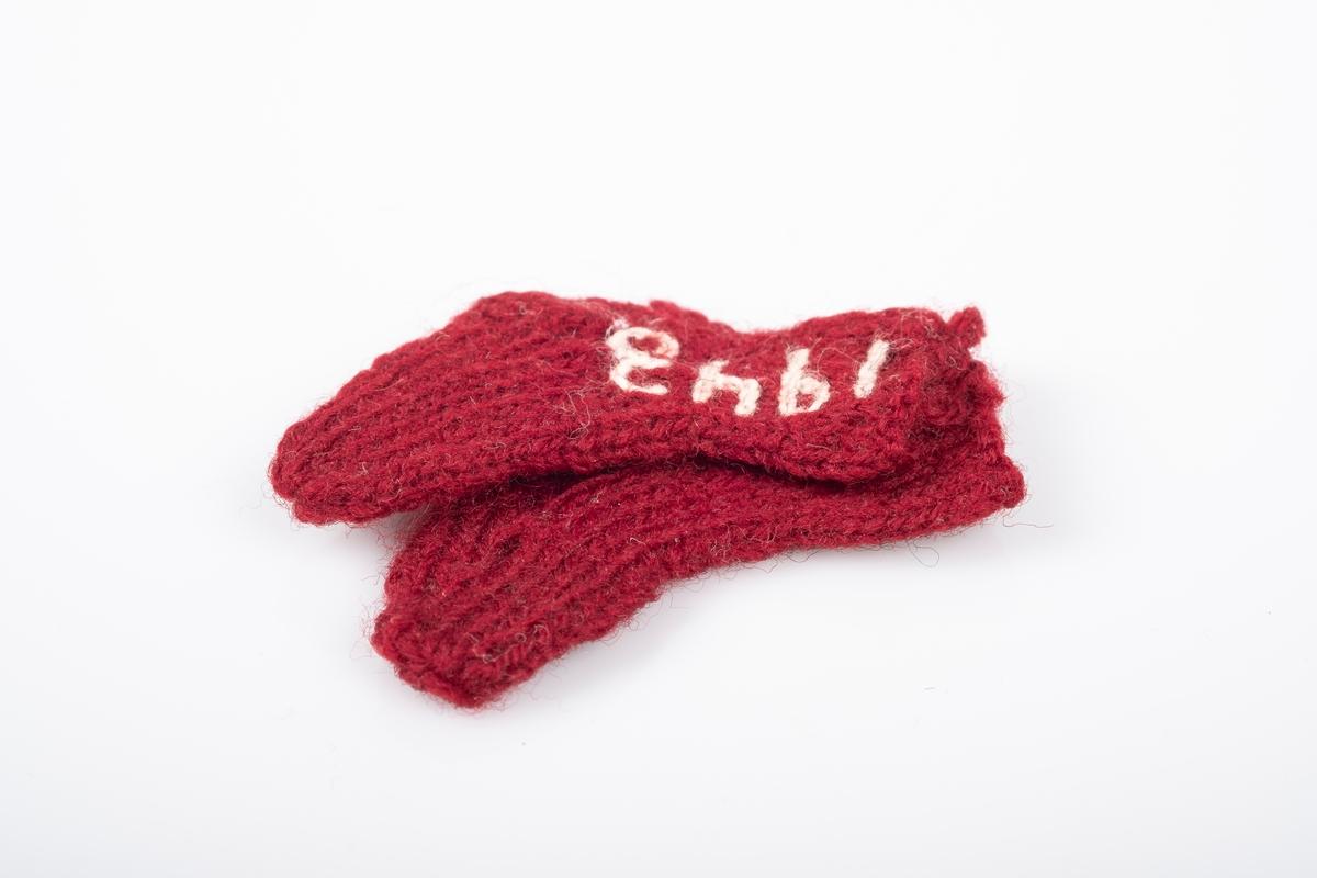 """Ett par strikket sokker som er bundet eller sydd sammen. Sokkene er strikket med garn i burgunder. Det er brodert """"Grini"""" på den ene sokken og """"1943"""" på den andre, med hvitt garn."""