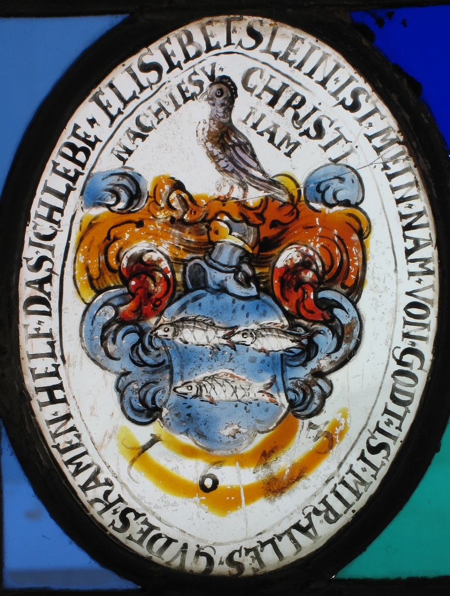 Blått våpenskjold med tre fisker, over hjelmen en fugl.  Omrammet av ranke i oker og blått med litt rødt.
