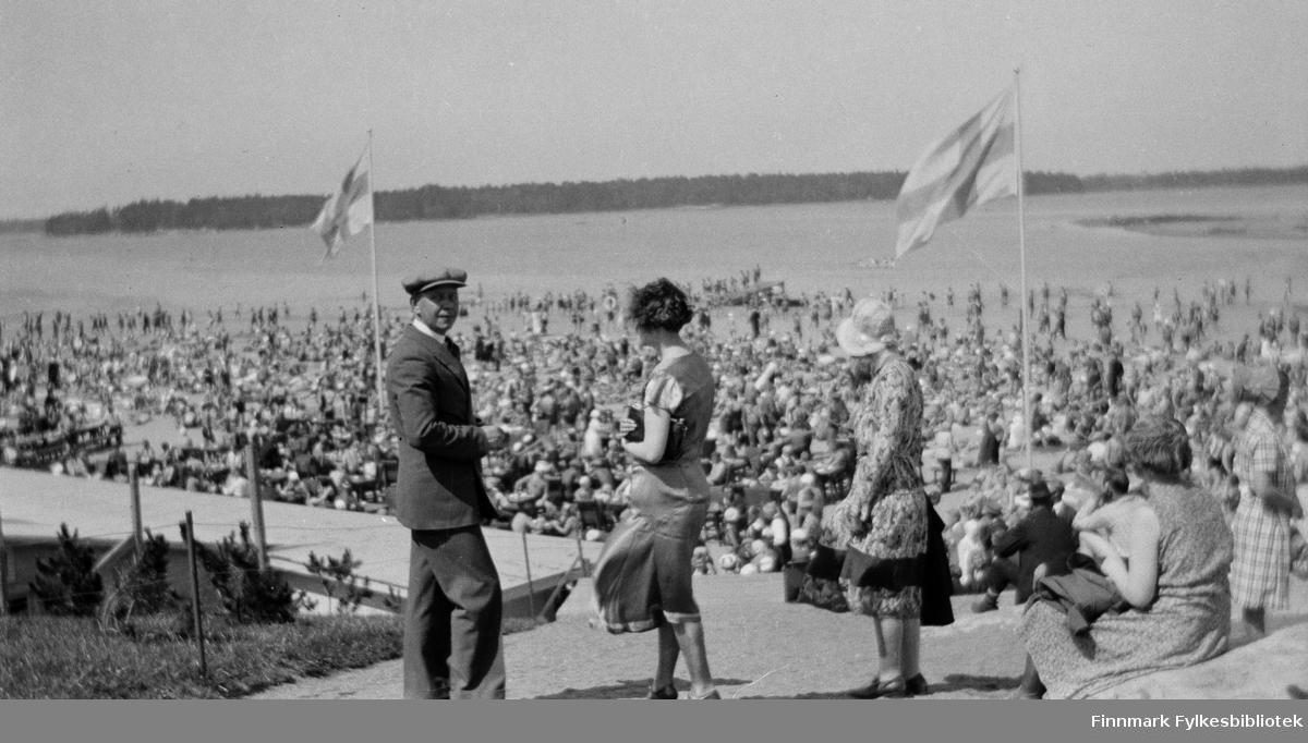 """Vardø-folk i reise i Finland. Lærerne Laura Lorentsen (senere gift Lilja) og Aslaug Alseen, og Oskar Alseen fotografert ved Sandudd badestrand (på finsk: Hietaniemen uimaranta, kalles også """"Hietsu"""") i Helsingfors. Bildet er tatt av Skodje, lærer på middelskolen. Finsk flagg er heist opp, folk har samlet å feire noe. Tidspunkt er juli i 1931."""
