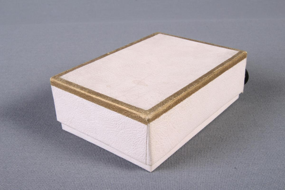 Knapper oppbevart i original eske med lokk.