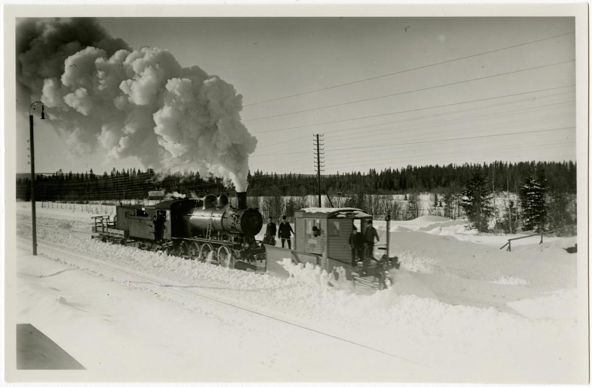 """Statens Järnvägar, SJ  Vingplogen i arbete å bangården i Jämtlands Sikås vintern 1936.Obs! plogens """"nosvinge"""" är utfälld."""
