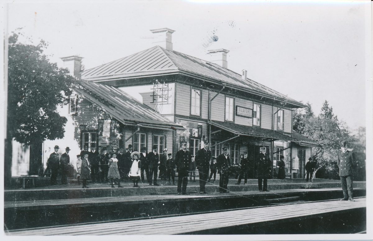 Sommarbild tagen från tidigt 1900-tal på Kilafors Järnvägsstation där flertalet resenäreer och tågpersonal inväntar anklommande tåg. Spåret är ännu inte elektrificerat varpå ånglok brukades.