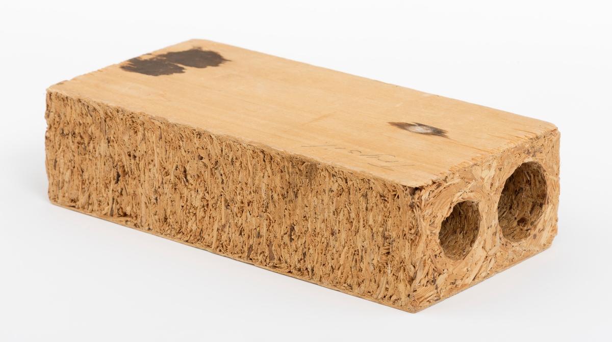 En rektangulær sponplate, kanalplate, vareprøve, på 15 cm x 7,6 cm x 4 cm. Plata har glatt fram- og bakside.  På vareprøvas ene side er det påskrevet med blyant Trysil. Det er borret 2 hull (kanaler) med diameter på henholdsvis på 25 og 18 millimeter i sponplata. De to kanalene i vareprøva er til gjennomføring av rør (ledninger).