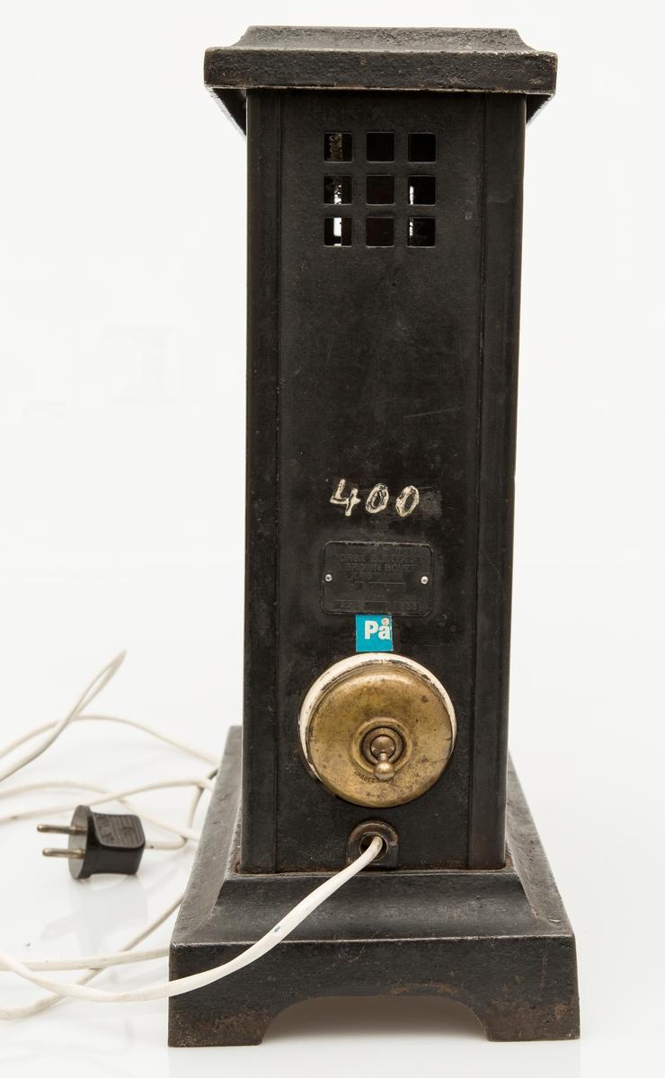 Elektrisk varmeovn. Høy og smal, støpejernsokkel med 4 ben. Bryter på siden, nyere kabel.