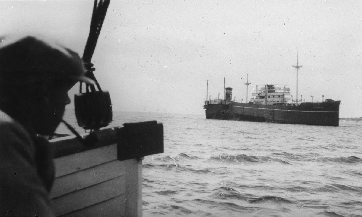 Motorskip sett fra dekk på et annet skip. Del av redningsbåt og overkroppen på en mann til venstre i motivet
