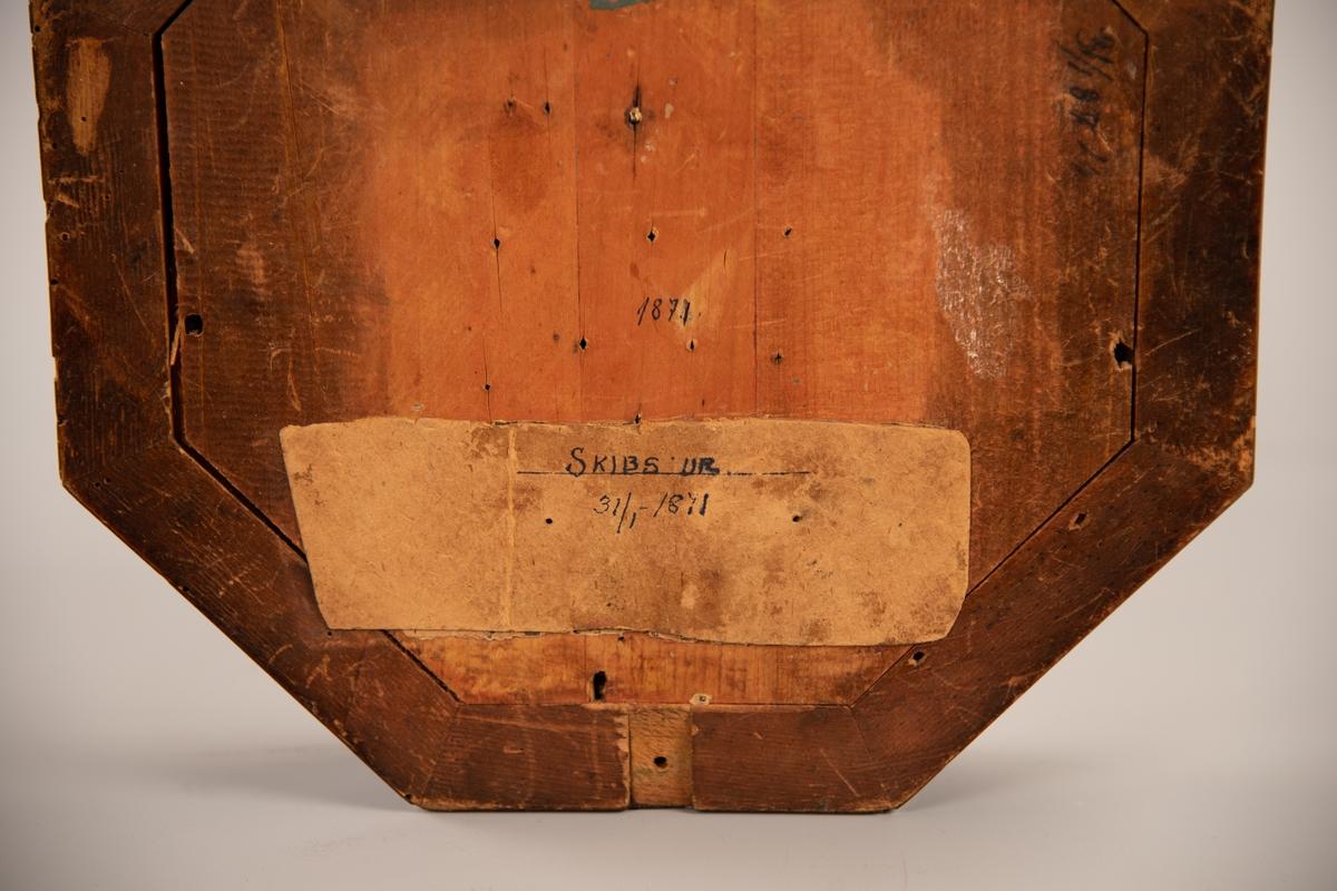 """Åttekantet skipsur i trekasse. Glasset foran urskiven kan åpnes med en mekanisme ved siden av 9-tallet. Urskiven er påmalt romerske bokstaver. Urskiven har også en sekundviser. Opptrekkeren ligger løst inne i klokken. Til den er det festet en liten lapp til med hyssing hvor det står """"Skibsur """" på.  Ingen firma/bedriftsmerker på klokken. På urkiven er det to hulll for opptrekksnøkkelen."""