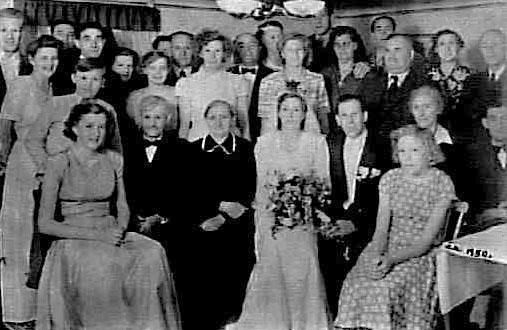 """Ett brudpar med gäster på Grankärr i Götlunda 1950. Bruden heter Birgit Karlsson.Den """"korpulente"""" mannen på höger sida är Verner Österlind, Österås, Grankärr, Götlunda. Nedanför sitter Anna Karlsson, Grankärr,                         ytterligare till höger (halva ansiktet skymd) hennes man, Erland Karlsson."""