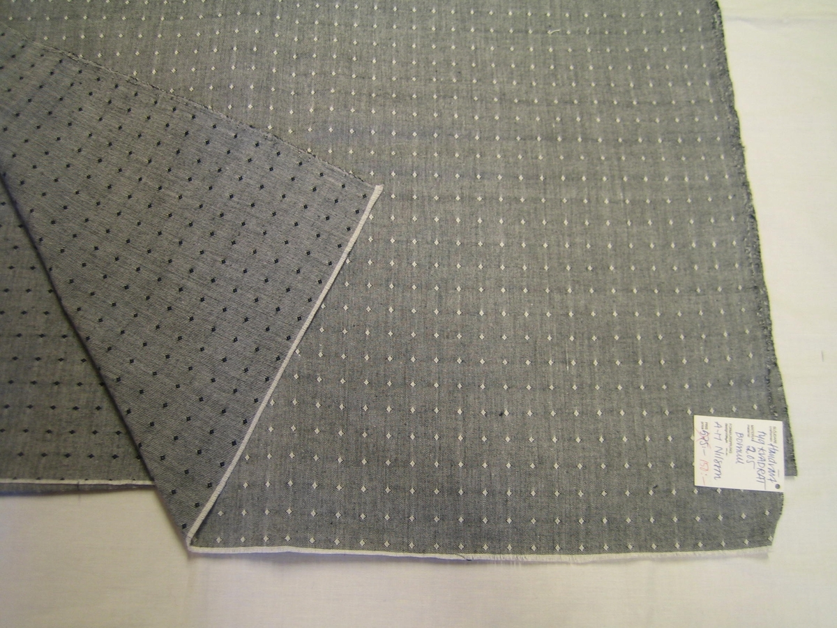 """Posten består av tre vävprover i tyget KVADRAT i tre olika färställningar med vit varp och en med svart inslag, en med blått inslag och en med rött inslag. Vävt i tuskaft med en romb i färgeffekt. Tyget är tänkt till kläder och är i bomull.  På det svartvita tyget är en lapp fastsatt med texten: """"Handvävt tyg KVADRAT, Material 2,05 Bomull, Design A-M Nilsson Pris 575:- överstruket, 150:-. Länshemslöjden SKARABORG SKÖVDE"""""""