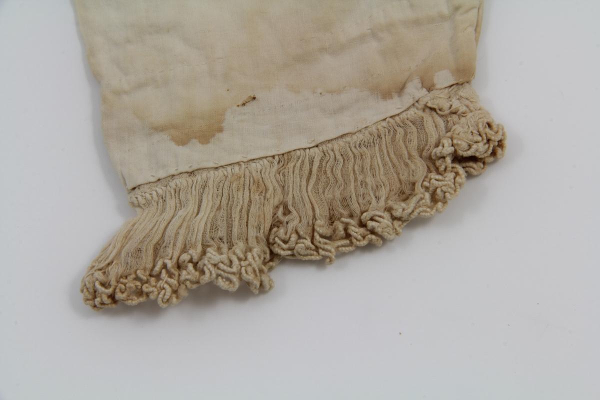 Hvit bomullskjole, hvite bendelbånd av lin, hvitt bomullsbroderi. Åpning bak, lukket med trekksnor i livet ved halsringningen. Skjørtet sydd av ett tøystykke, rynket fast til livet som er sydd av ett forstykke og fire bakstykker. Lange, isydde ermer. Meget vid halsringning med løpegang for trekksnor. Bredt tøystykke med hvitsøm broderi nederst festet langs halsringningen og nederst på skjørtet. Rysje av gjennomsiktig bomullstøy med brodert kant nederst på ermene. Ermene foret, livet delvis foret.