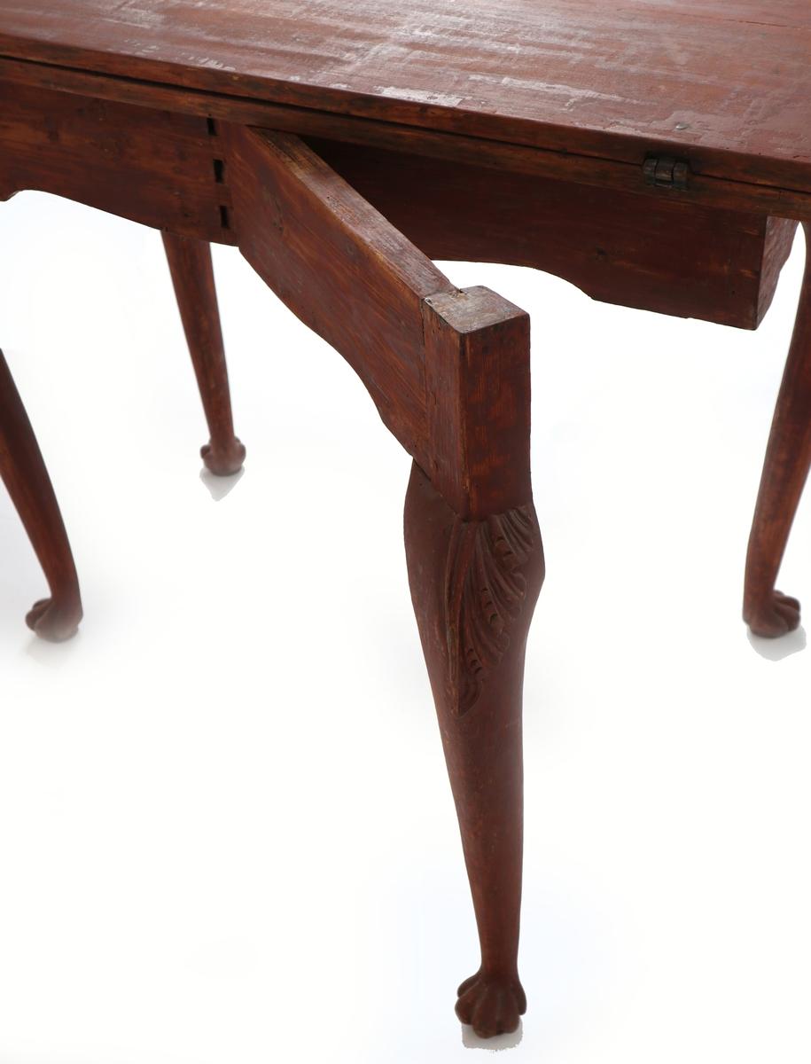 """Spillebord, rokokko,  Furu.  Tidlig, régence-preget rokokko, med buede ben med  kraftige, Chippendale-lignende knær m. utskåret blad  og med fot m. 5 tær som en dyrepote, uten klær. Buet  og tunget sarg, i fronten utskåret motiv: stor rosett-blomst flankert av to hundelignende fabeldyr med  bakkroppen endende i en volutt. Dobbel bordplate, hengslet i bakkanten, med profilert kant, forkrøppet  på hjørnene. Bordets venstre bakben kan svinges ut  og bordplaten brettes over, hvorved bordflaten måler  90 x 96,5 cm.  Tilstand mai 1960: sortmalt, med ornamenter og føtter forgylte. Under den sorte maling: et lag sparkel.  Under sparkel: den opprinnelige farve: rød beis eller  tynn maling, sannsynligvis det såkalte """"drageblod"""". Under dette: treet.  Den sorte maling avskallet og stygg, vablet og ujevn.  Forgyllingen tildels anløpen. Bordplatens øvre del sprukket i limingen, helt løs. Bordet er litt angrepet  av tremark.  Tilstand jan. 2018: Rødmalt med """"drageblod"""" etter restaurering på Aust-Agder-Museets snekkerverksted mellom 1965 og 1993."""