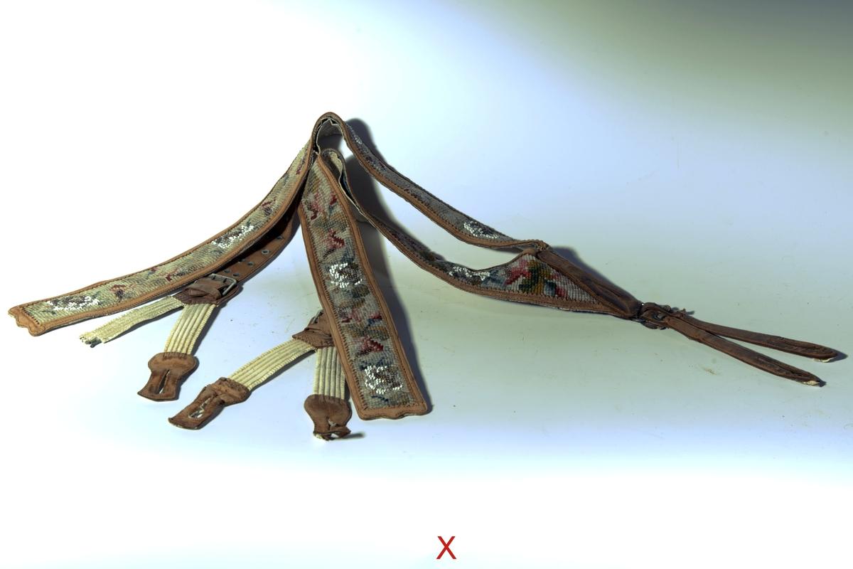 Litt perler, lysbrune skinnkanter, hvitt skinn på baksiden, rem med 2 x 6 hull  foran på hver side. I ryggen 2 remmer med knapphull, spenne, 2 remmer med strikk og knapphull.