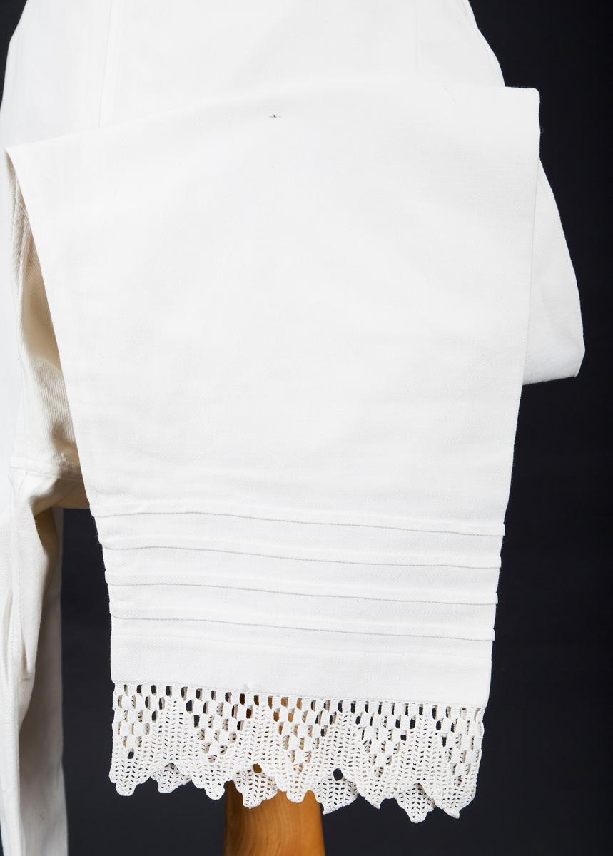 Hånvevet bomullstoff. Splitt i sidene. Kiler midt bak. Forlenget linning,  knapphull eller trådknapp i endene. A brodert med røde korssting på linningen midt forran. Nederst på bena 4 smale legg og heklet blonde.