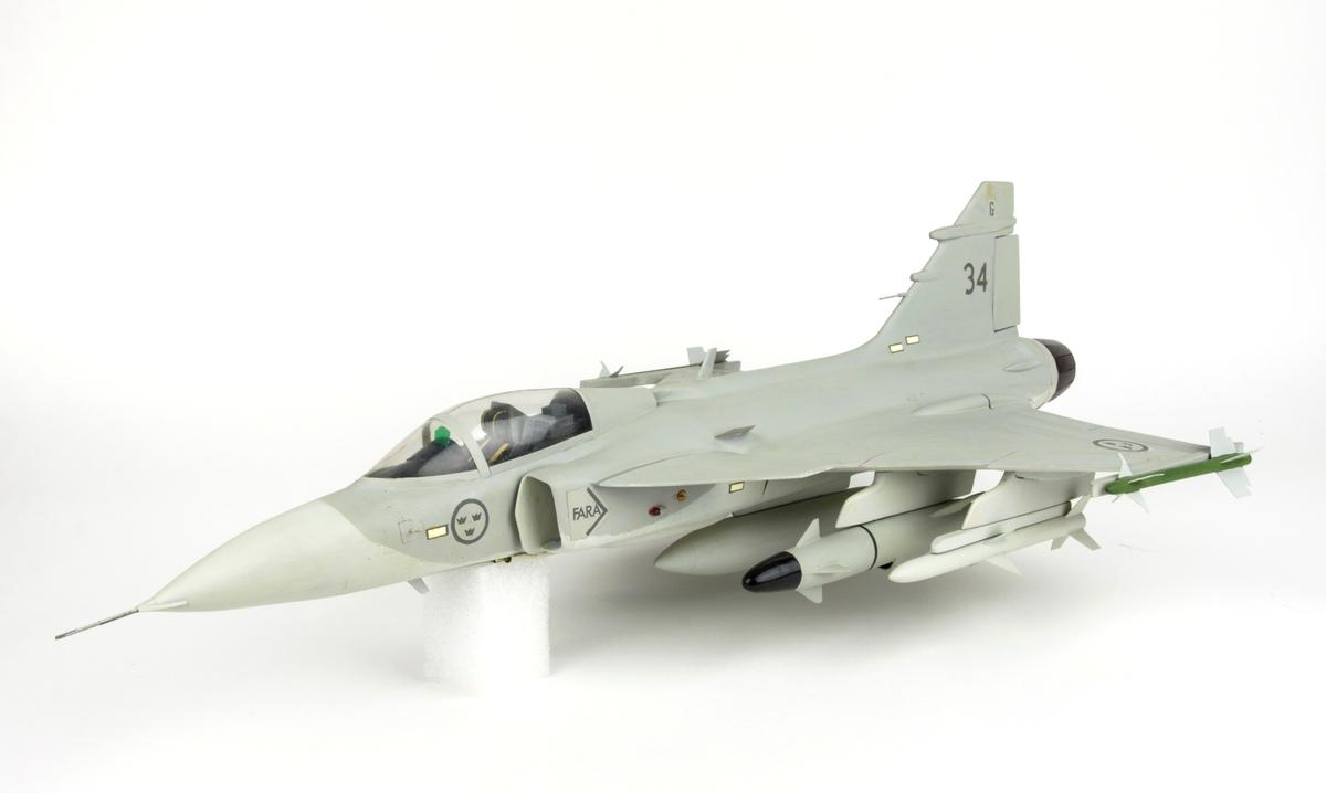 Flygplansmodell av JAS 39 Gripen. Flygplansmodellen har nummer 34 på fenan. Gråmålad och märkt med svenska kronmärken i ljus- och mörkgrått. Modellen har utfällningsbara laddningsställ och visar Gripen utrustad med beväpning. Skala 1:24.