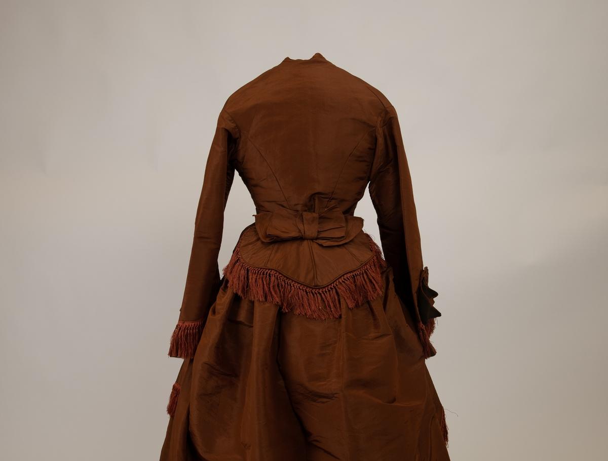 Den kjolen i brun silke består av fire deler: jakke, et skjørt, et overskjørt og et belte med sløyfe bak.  Kjolen er håndsydd bortsett fra et smalt kanteband som er nederst på skjørtet. I denne perioden brukte man ofte to seperate skjørt, som her, der overskjørtet var hovedkilden for dekorasjonen. Her har overskjørtet påsydde silkefrynser. Sløyfedetalj neders på jakkens ermer.  A) Skjørt. Sydd av syv lengder, de to bak har tett rynkekant øverst mot den smale linningen av lin. Skjørtet kantet nedentil invendig med 16 cm. bred stoffkant.   B) Forknappet overdel. Fem trukne knapper og to hekter. Avskåret i livet, hele forstykker med et innsnitt på hver side. Rygg med to buede sidesømmer. Kraveløs.Vide ermer, sterkt skrånede. Pynt neders med 7.5 cm lang frynse. Over frynsen en sløyfe av stoff. Overdelen er håndsydd, og foret med hvit og lysebrun lerret.  C) Kort overkjole . polonaise. Sydd av tre lengder med kiler i sidene nede.  Kort rundet forstykke. Sidere buet bakstykke med  siderynker for tournure. Kantet nede med frynse som på ermene. Moten ble lansert i Paris 1867.   D) Sløyfe.  Hjerteformet stykke stoff kantet med frynser og pyntet på med en sløyfe i stoffet, med bånd til å knytte rundt livet, over polonaisen.