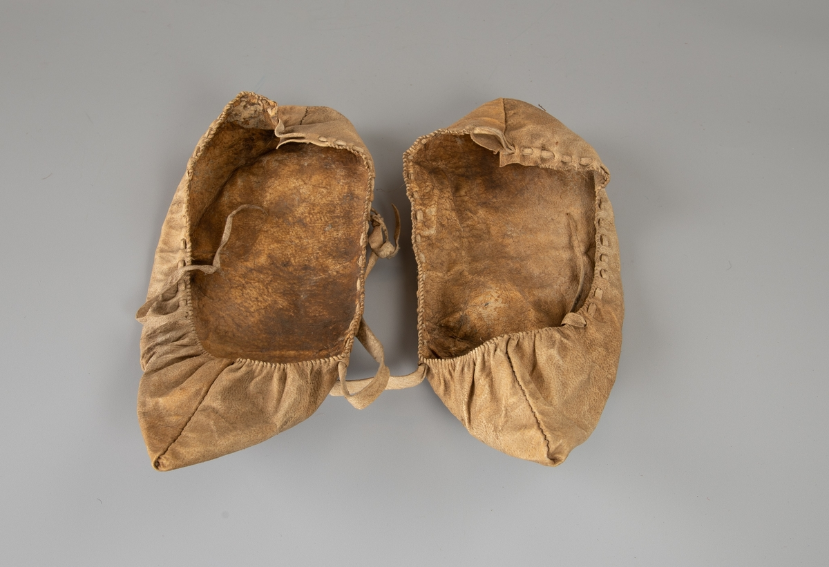 To mokkasiner i stivt materiale, sydd av ett stykke med søm midt bak og i tåen. Kastesøm langs kanten. Hull for snortrekk under  denne med en tynn lys skinnrem trukket igjennom.