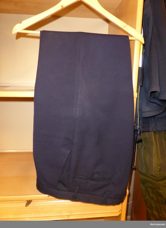 """Två kolli med uniformsrock, byxor, och midjejacka. Tillhörigt """"Stor-ben"""". Kläderna är mörkblåa med guldfärgade detaljer. Midjejackan är storlek C48, den mörkare byxan med kraftigare tyg har storlek C48, medan den andra byxan har storlek 50C."""