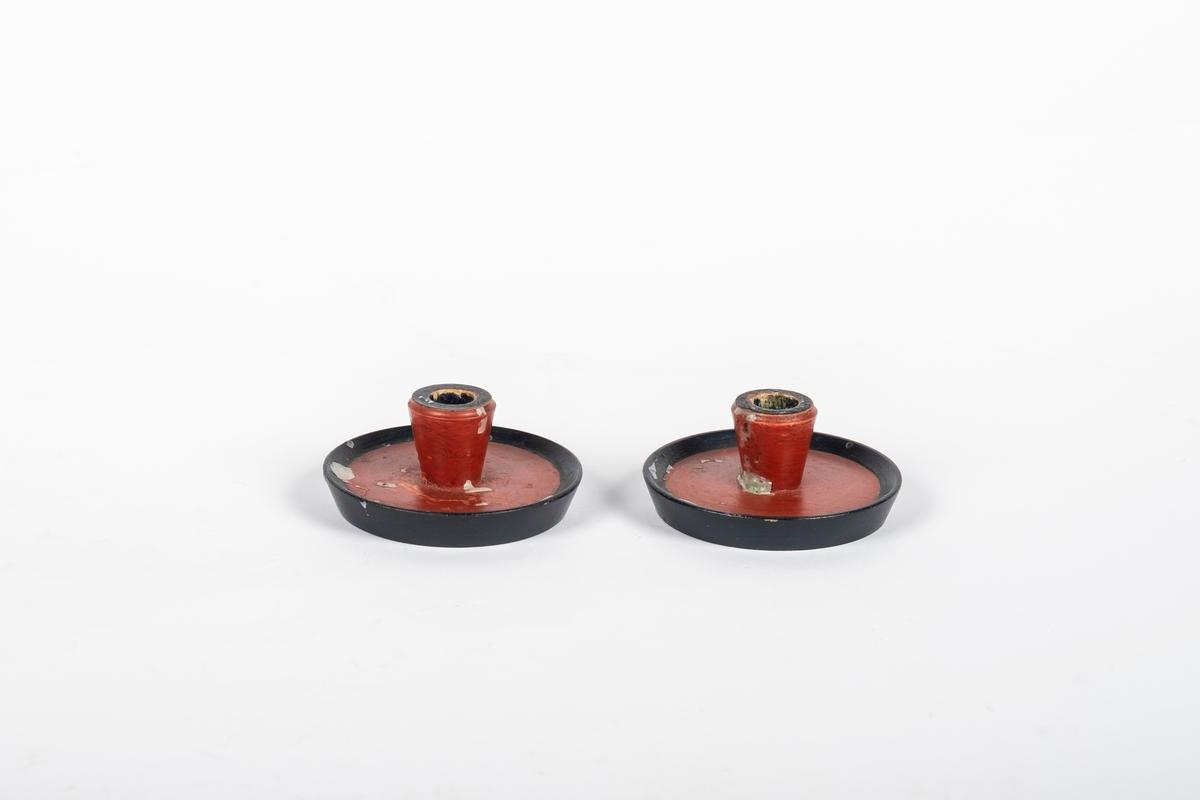 2 runde lysestaker i tre som er malt rødt og svart. Den har rundt flat skål til fot.