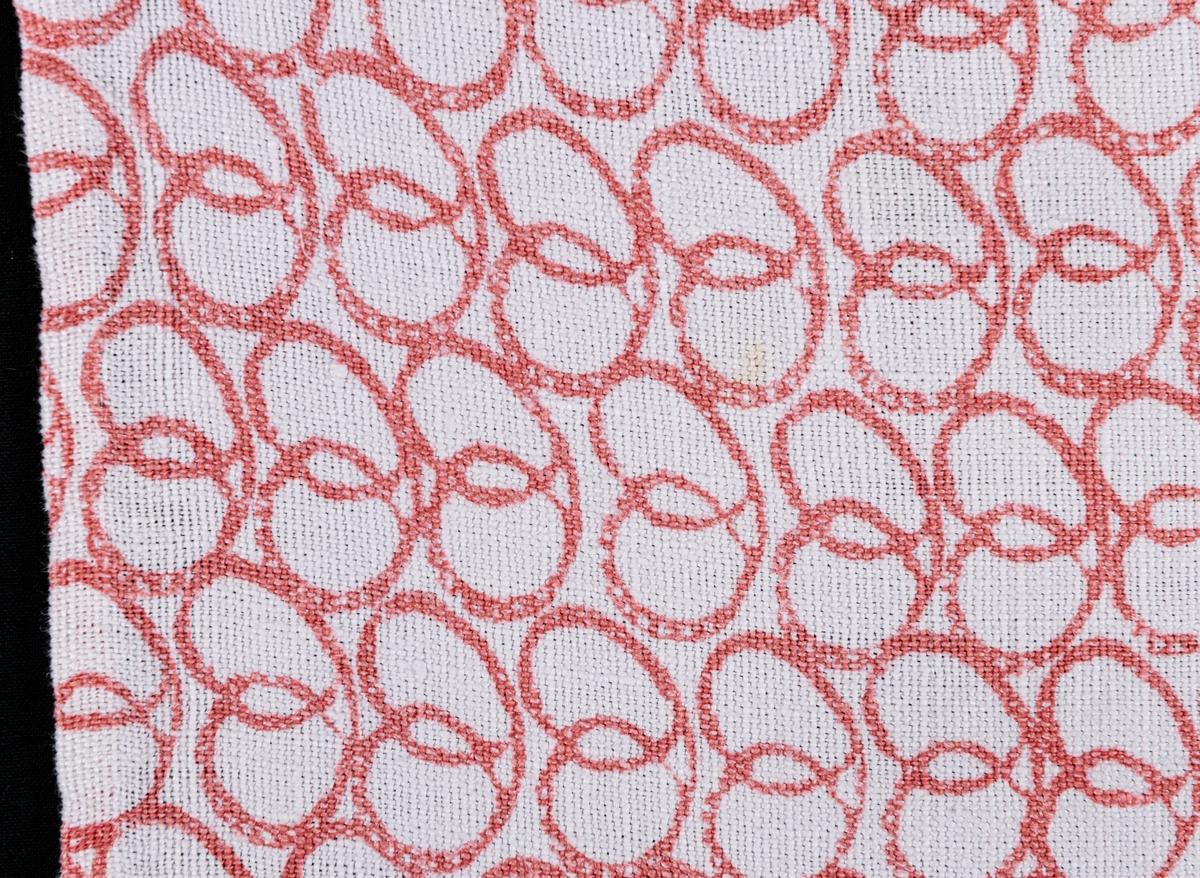 """En gardinvåd av bomull med handtryckt mönster, rött mot vit botten. Kallas """"Kringlan"""" eftersom mönstret är i form av kringlor. Vävt av Jobs i Leksand för Gefle Ångväveris räkning i slutet av 1940-talet eller början på 1950-talet. Några fläckar."""