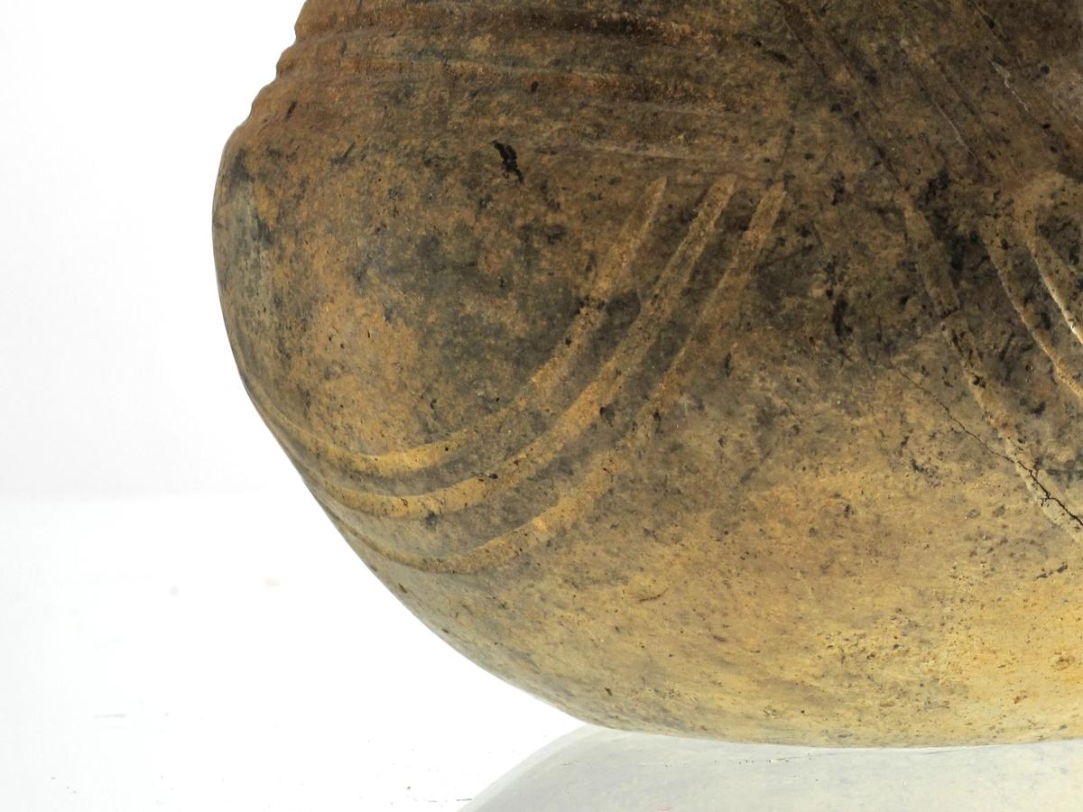 Leirkar av lys brunlig, godt brent, tynt gods med profilog ornering nærmest som Bøe: Keramikk, fig. 86, men uten hulkiler. Karet har kort, reist hank (sml. fig. 75), som er ornert med 4 vertikale linjebunter, nederst avsluttet med en horisontal linje. Karet er meget pent forarbeidet. En del av randen mangler, ellers godt bevart.