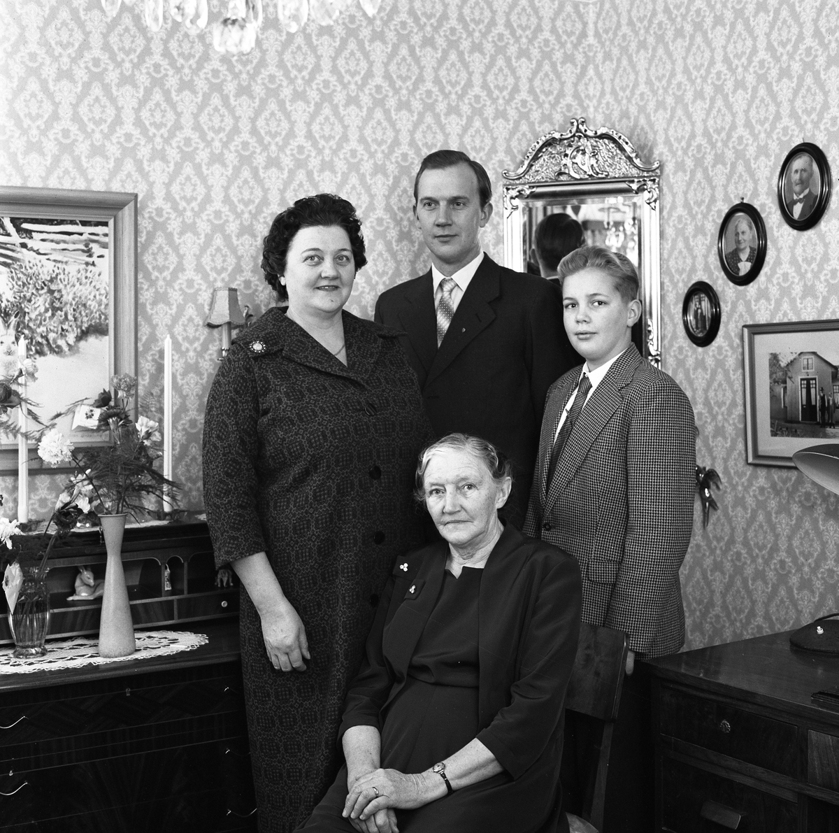 Fyra generationer. Augusta Gustavsson (sittande) är född 1881. Hennes dotter, Ingegärd Karlsson, är född 1906. Åke Johansson är född 1925 och hans son, Per-Åke Johansson, är född 1945. Åke körde lastbil åt sin styvfar Evert. Per-Åke blev polis. Bilden kan vara tagen på Trädgårdsgatan 19. En sekretär står till vänster och en stor spegel ses, på väggen, bakom gruppen. Evert Karlsson, Trädgårdsgatan 19
