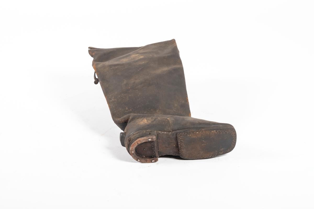 Støvelen er høy og blir videre mot toppen. Skotuppen er rett og skrår oppover. Bak på hælen er det sydd/spikret på en trekantet lærbit som står ut. Under hælen er det naglet på en halvsirkel av metall, lik en liten hestesko. Det er et snitt bak på støvelhalsen. Opp fra støvelens innside stikker det to brede lærremmer, muligens til å trekke på seg støvlene med. Materialet er mykt og kraftig. Bak på støvelen henger en lærdusk.