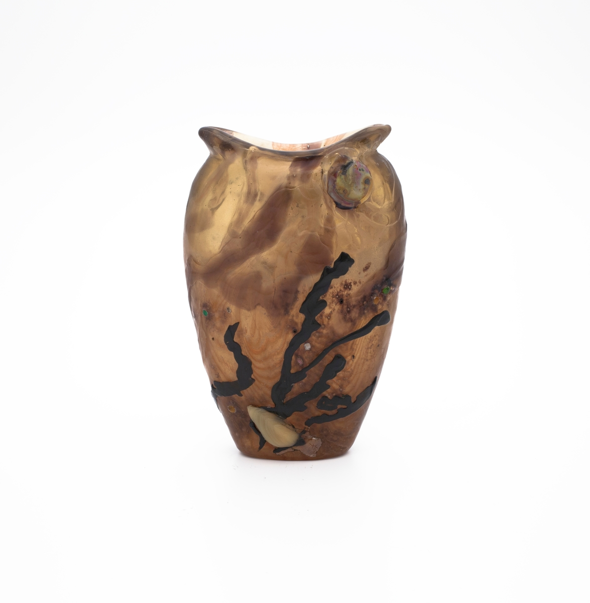 """Vase i overfangglass. Ellipseformet og flattrykket korpus med en meget vid åpning. Formen minner om et gapende fiskehode, hvis øye er plassert på forsiden i form av en mørkerød glasskule. Vasen er støpt, og deretter skåret i overfangsteknikk. Den består av en tykk masse av sammensmeltede glasslag i ulike farger og sjatteringer. Korpus har en røktopaslignende overflate, dekorert med sorte og lilla alger, derav algues (fr. alger). På arbeidet er det inkrusteringer i form av gule og grønne glassperler. Baksiden av vasen er gravert med innskriften """"Gallé Expos.on 1900"""", samt """"et nul vent ne détruit son fragile univers"""" (fr. og ingen vind ødelegger dets skjøre univers),  sistnevnte et sitat fra den belgiske poeten Rodenbachs diktsamling Les vies encloses (1896)."""