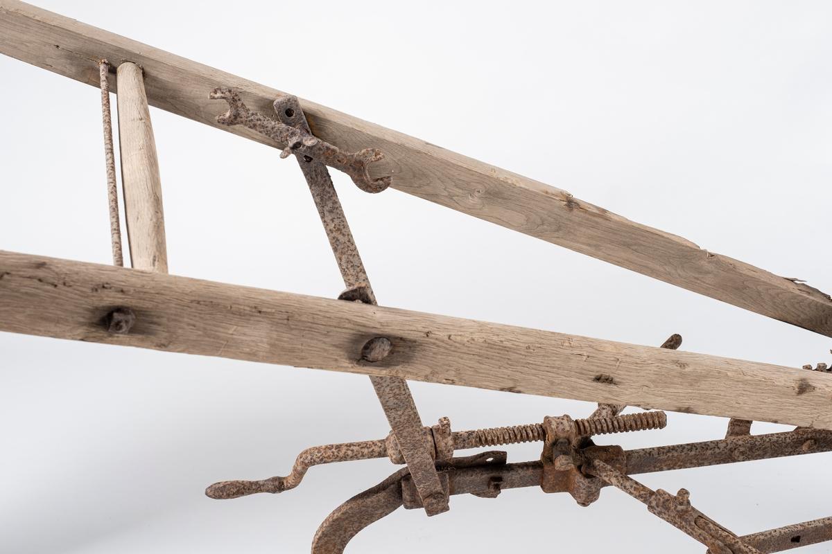 Plog til spredning av møkk. To separate styrestenger av tre, med jernforsterkning på oversiden av håndtakene. På innsiden av venstre styrestang er det festet en fastnøkkel. Ås av jern, med plog og hjul (foran), ett sveivehåndtak og en hendel, også av jern. I front av plogen er det i kjetting festet et tverrstykke til trekking av hest.