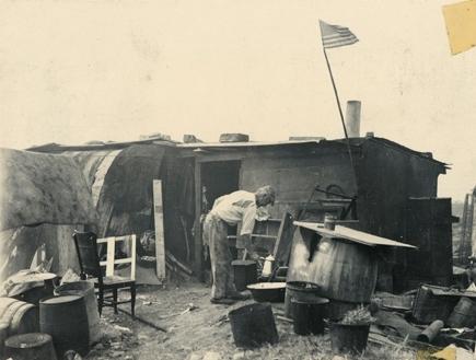 """Eldre mann med en kaffekanne utenfor boligbrakke i """"Ørken Sur"""", Brooklyn NY, ca 1929-1935. Amerikansk flagg heiset på bambusstang ved døren."""