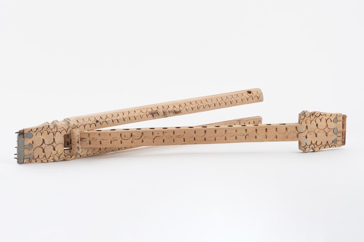 Vevspenne av tre som består av to deler. To staver er satt sammen, den ene inni den andre. Lengden kan opprinnelig reguleres. Det mangler en trepinne, og de to delene kan tas fra hverandre. Vevspenna har utskåret bølgeformet dekor og utskjæringer i endene. Den har også en utstkåret knott tappet inn på oversiden av den ene enden. Det er beslag av metall i hver side av vevspenna, men det kun pigger i den ene siden. Den andre siden har hatt pigger, men disse mangler.