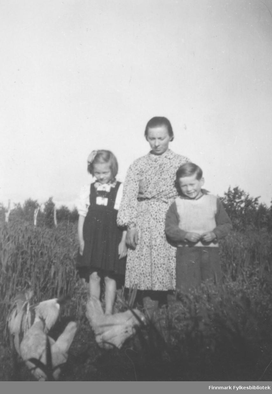 En kvinne og to barn fotografert på et jorde i Oterbekken i Nesseby. De er Anna Agnethe Mathisen, hennes mor Bigga Iversen Mathisen og Reidar Mathisen.
