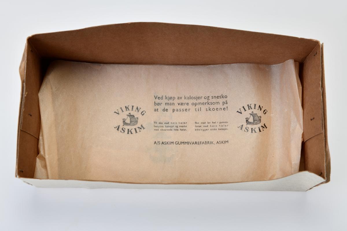 Sorte dame kalosjer med høy hel. Foret med trikotstoff. Tekst på undersiden av skoen. Disse oppbevares i en skoeske med tekst. I esken er det en liten kontrollseddel og et langt smalt ark med tekst. Håndskrevet pris på etiketten på esken. Esken er stiftet sammen i hjørnene. Uoriginalt lokk på esken.