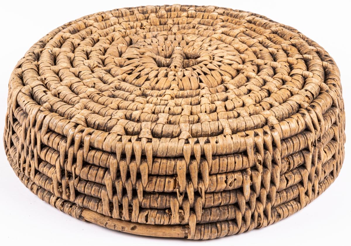 Korg, rund, grov flätning med virade pinnar. litet hål i botten med kors.