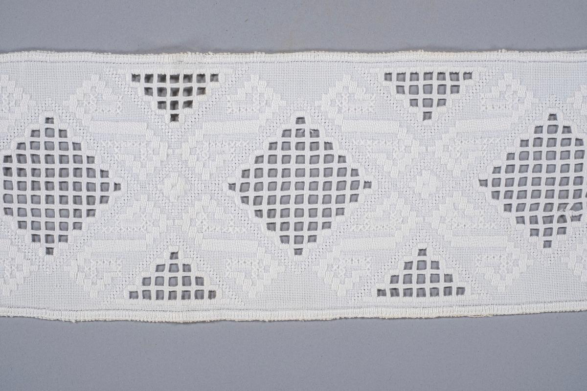 Hvitt mellomverk med brodert hardangersøm. Det er rombe- og trekantformet mønster langs mellomverket.