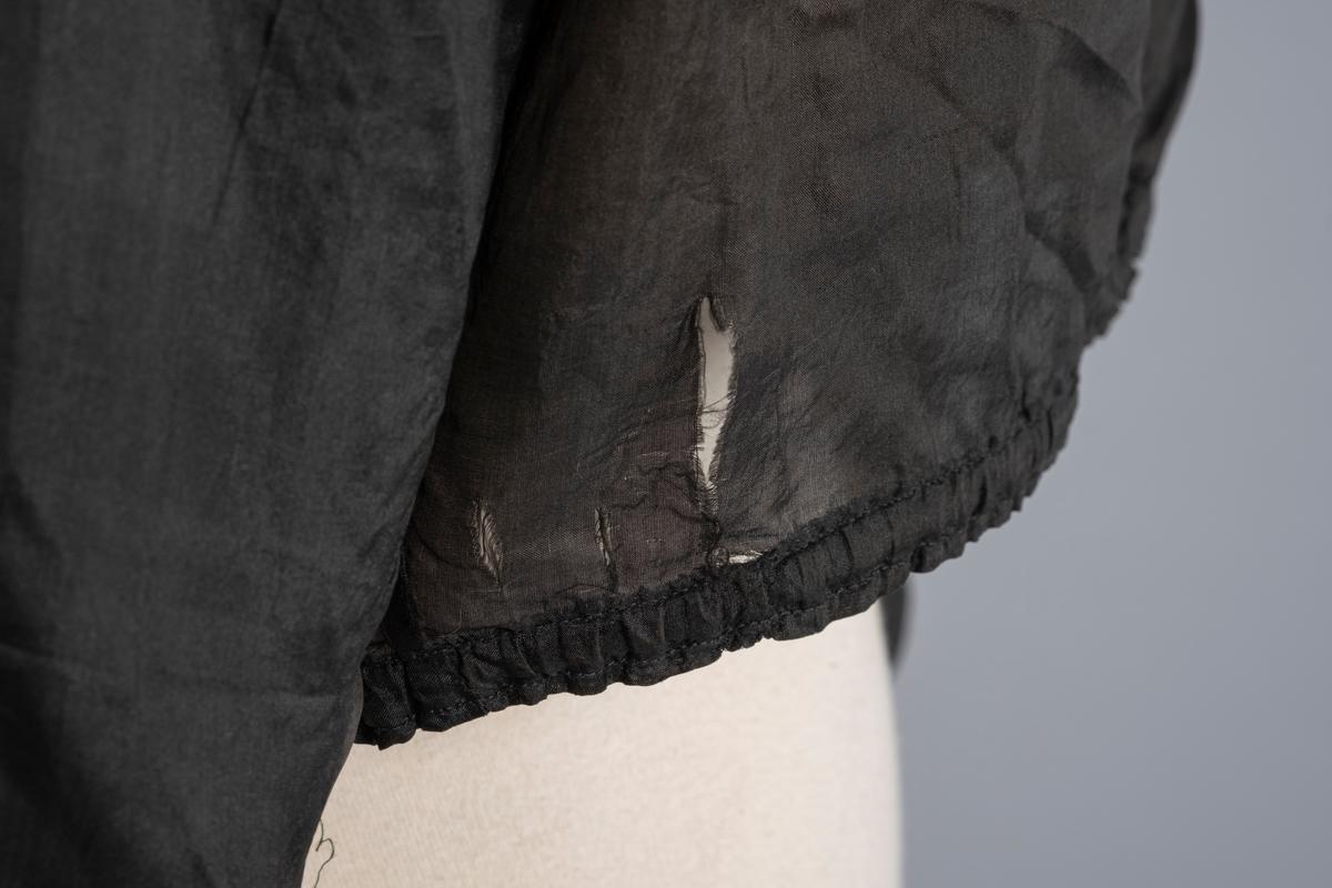 Svart silkebluse med lange ermer. Det er åpning i front helt ned som lukkes med 8 knapper. Fra skulderstykket til livet går to loddrette partier med 6 biser på hver. Nærmere ermet på hver side går to loddrette partier med 4 biser kun ned til bysten. Blusen er rynket i livet.