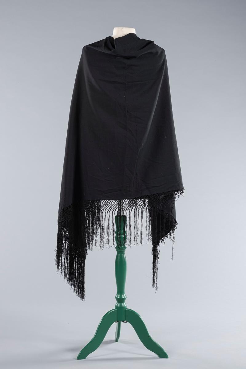Svart sjal i bomull, kantet med lange frynser i myk bomull, i en kombinert flette- og knyteteknikk.