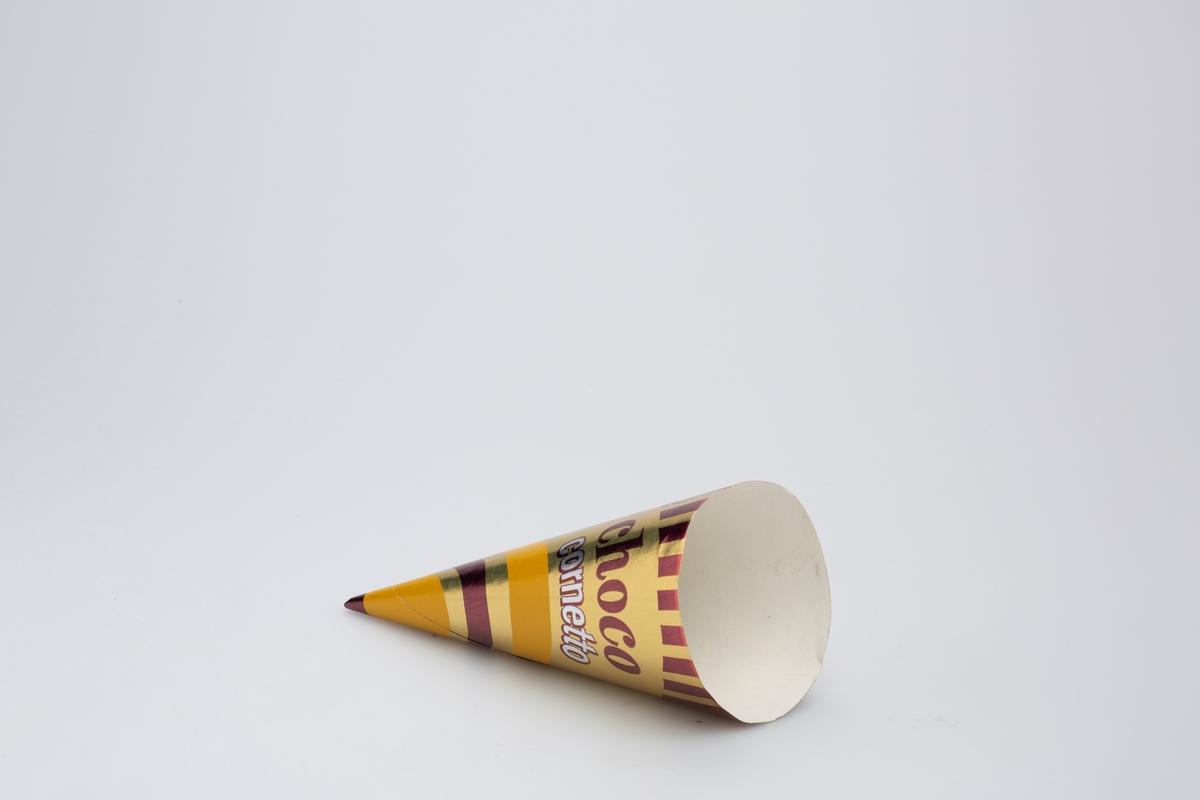 Kjegleformet iskrempapir (kremmerhus) i aluminium. Kremmerhuset er med farger på utsiden, og matt uten farge (hvit) på innsiden. Iskrempapiret har gullfarget bakgrunnsfarge, med noen bølgete linjer i gult og brunt i nedre del. Øverst er det vertikale tette brune streker. Tekst er plassert på et belte av gull i øvre del. En stiplet linje markerer en rivekant i papiret.