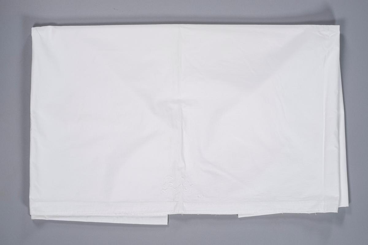 Hvitt laken med broderte initialer.