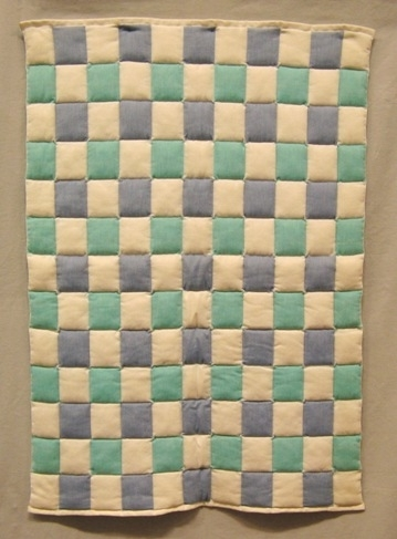 En rutmönstrad dubbel väv i tuskaft tänkt som babytäcke. Man har fyllt rutorna med syntetvadd under vävningens gång. Varpen är av tvåtrådigt bomullsgarn i blekt, blått och blågrönt. Varannan ruta är vit och varannan färgad.  Se även inv.nr 0034:2 Vävprov till babytäcke i vitt, gult och rosa.  Täcket är märkt med R34:1 på ett vitt bomullsband.  Täcke med modellnamn Rymd är formgivet av Ann-Mari Nilsson och tillverkat av Länshemslöjden Skaraborg. Det finns med  på sidan 80-81 i vävboken Inredningsvävar av Ann-Mari Nilsson i samarbete med Länshemslöjden Skaraborg från 1987, ICA Bokförlag. Se även inv.nr. 0001-0033,0035-0040.