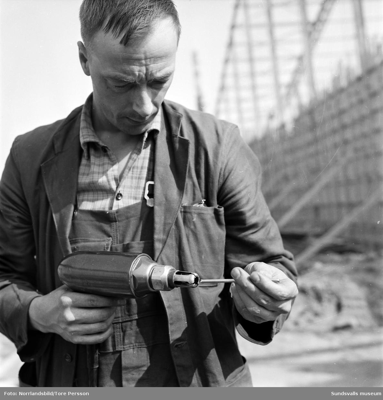 Bygget av isladan i Timrå, takstommen står klar. På bild två en av byggnadsarbetarna.