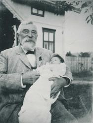 Eldre mann i dress sitter utendørs med en baby i armene.