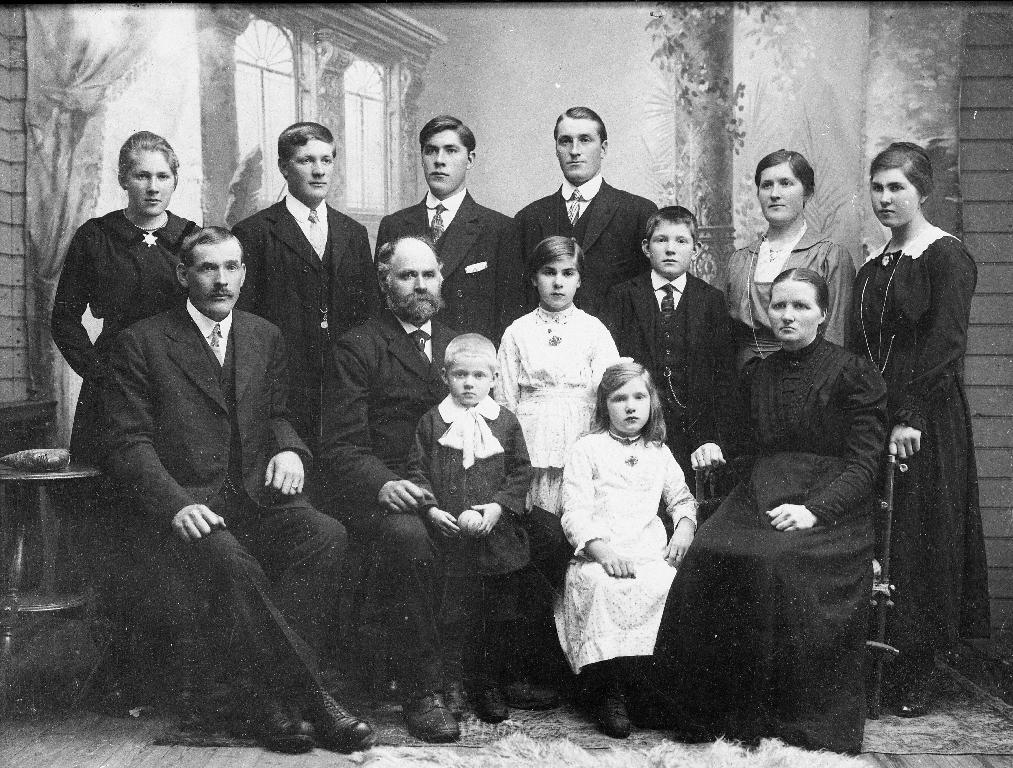 Familiebilete av Karen og Ole Bergene med 11 born. Framme f. v. : Ola Bergene (1889 - ), far Ole Bergene (1866 - ) med Johan Bergene (1913 - ) på fanget, ståande Jorina Bergene (1907 - ), sitjande Berta Bergene (1910 - ), mor Karen f. Øvestad (1866 -). Bak f. v. : Klara Bergene (1902 - ), Olaf Bergene (1895 - ), Sem Bergene (1897 - ), Torvald Bergene (1893 - ), Elling Bergene (1905 - ), Maria Bergene (1891 - ), Malena Bergene (1899 - ). Familien køyrde frå Kartavoll (Bergene) med to hestar og kjerrer for å få alle med til fotografen.