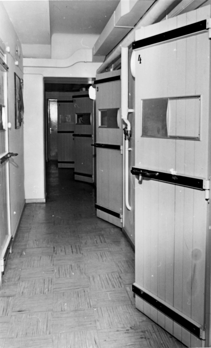 """Kasernvakten, omkring 1980  Arresterna låg vid kasernvakten i kasern 004 från slutet av 50-talet och ca 30 år framåt. Användningen under de senare decenierna var nog mycket litet.  Bild 1: De fyra arresterna ser vi här på höger sida av gången, de hade ett litet fönster för ljusinsläpp och vädring. Dörren på v sida är till """"fyllarresten"""" -- ett kalt rum med ett uppbyggt sluttande trägolv, en golvbrunn och en vattenslang. Okänt hur många som kunde sova ruset av sig samtidigt.  Bild 2: Vanlig arrest. Sängen låstes i uppfält läge dagtid. En rostfri toalett och handfat fanns också. OBS! bilden är arrangerad och personen var nog bara fotomodell."""
