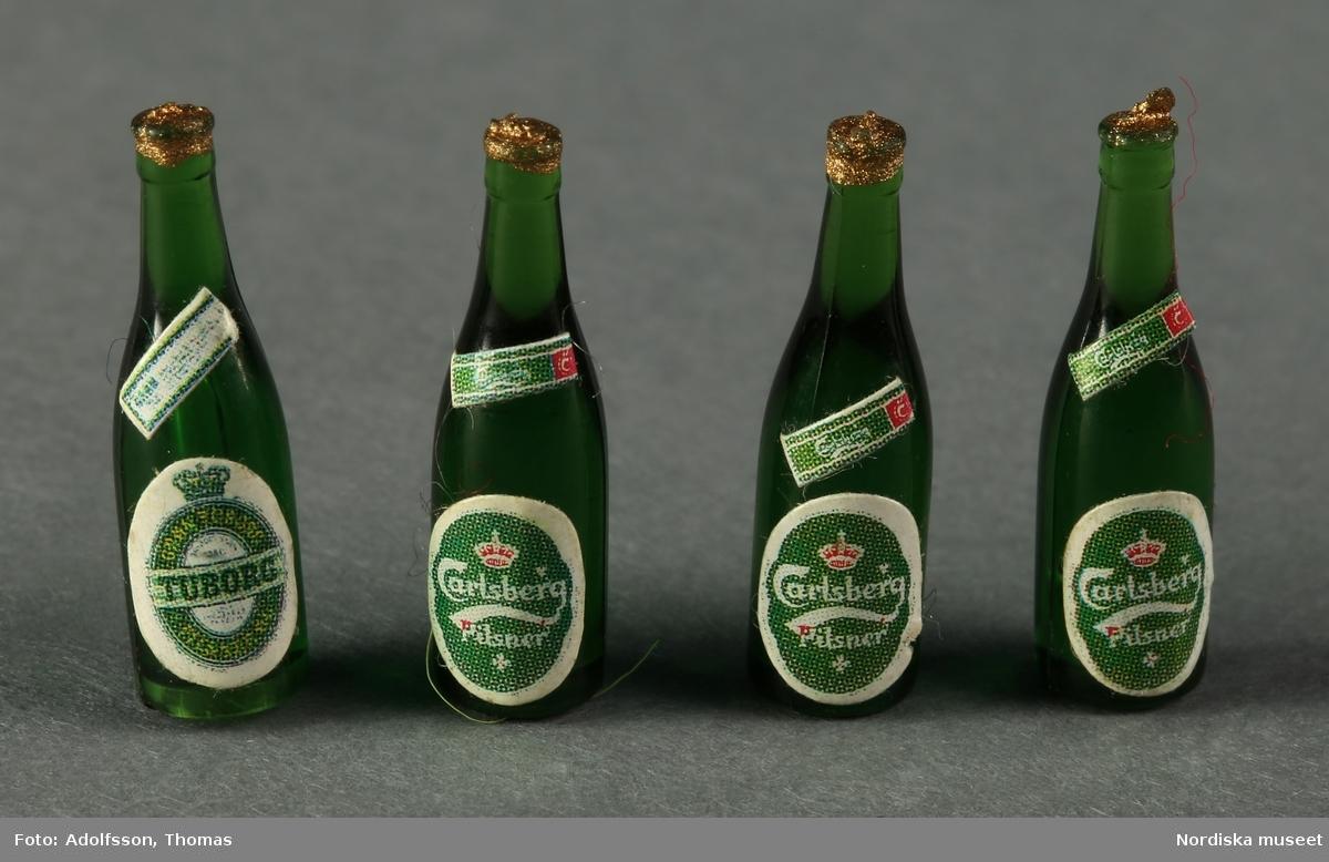 Fyra gröna ölflaskor av plast med etikett av papper. Avbildar dansk pilsner från öltillverkarna a) Tuborg (1 st.) och b-d) Carlsberg (3 st.). Hör till dockskåpsinredningen i matkällaren till dockskåp NM..