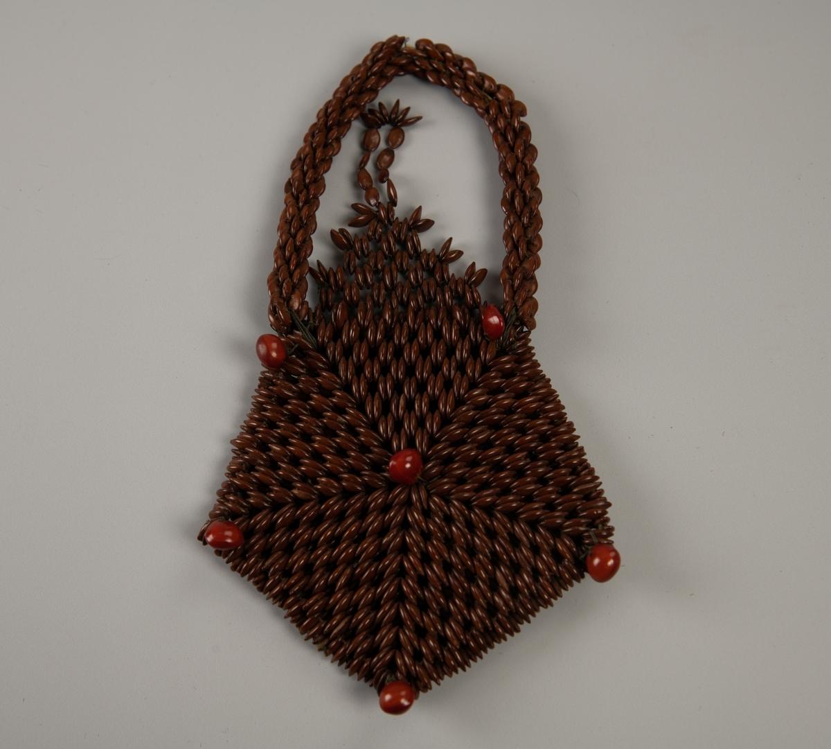 Femkantet pung som er flettet i fem trekanter med et rødt bær på midten og i hvert hjørne. Bakstykket er trekantet med hempe til å lukke med. Forholdsvis tykk, høy rundet hank av samme materiale.