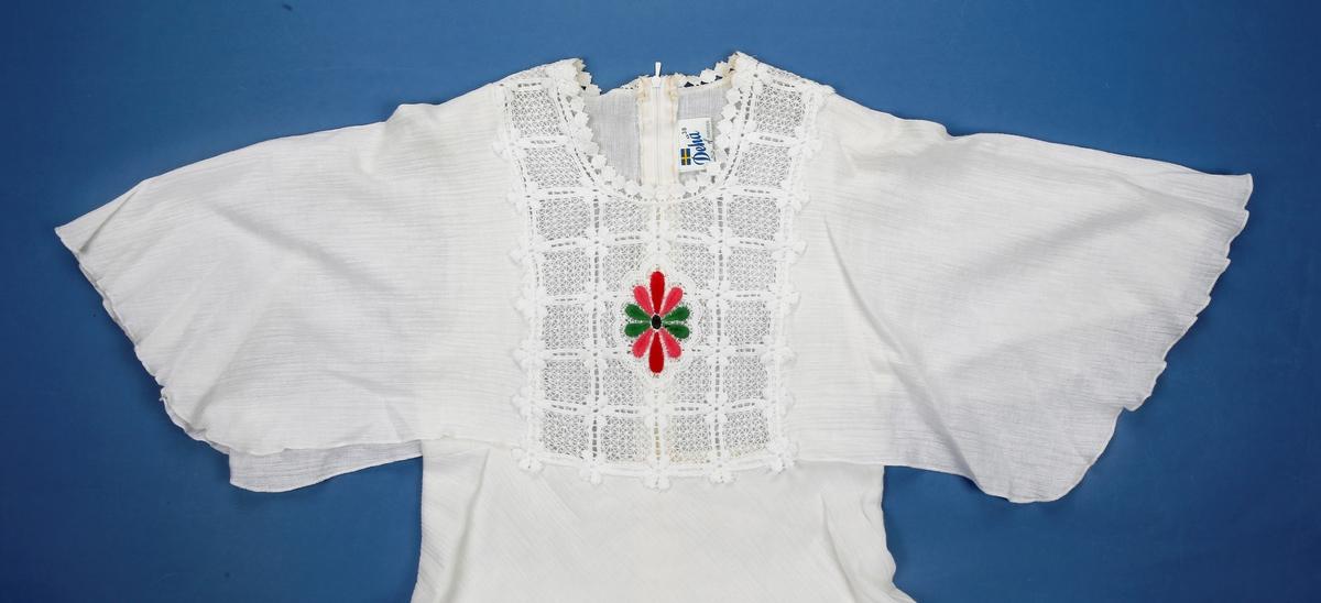 Hvit kjole med vingeermer. Blondepynt på brystet med rød og grønn blomst i midten. Skjørtet begynner under bysten. skjørtet består av to lengder over hverandre der den ene er kortere. begge lengdene slytter i spiss foran og bak. Glidelås bak.