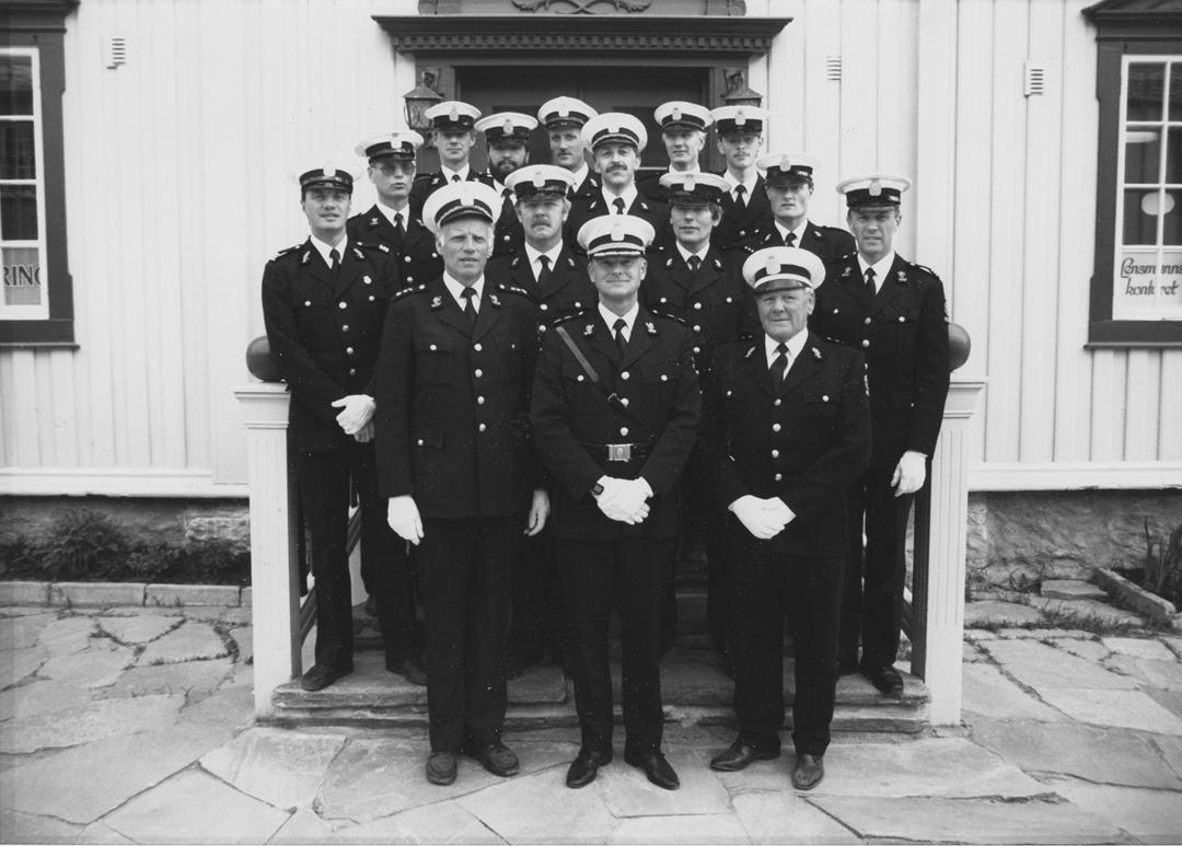 Femten uniformerte politifolk poserer utenfor et lensmannskontor. Trolig tilknytning til Uttrøndelag politidistrikt.
